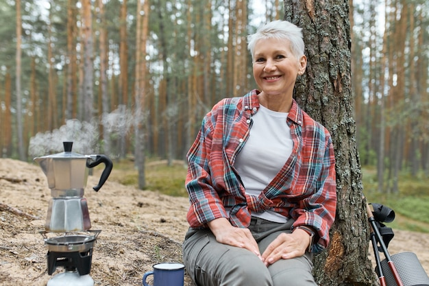 Camping lifestyle in forest. cheerful middle aged euroepan woman sitting on ground under pine going to make tea, boiling water in kettle on gas stove burner, having joyful happy facial expression