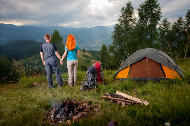 Camping. loving couple standing back near the fire, backpacks and tent