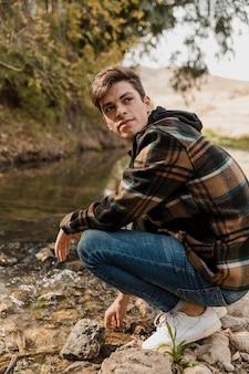 Uomo di campeggio nella foresta che si siede alla vista laterale del fiume