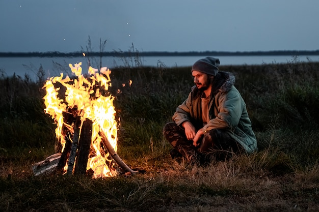 Camping man sitting by the fire at night against the sky.  travel, tourism, camping.