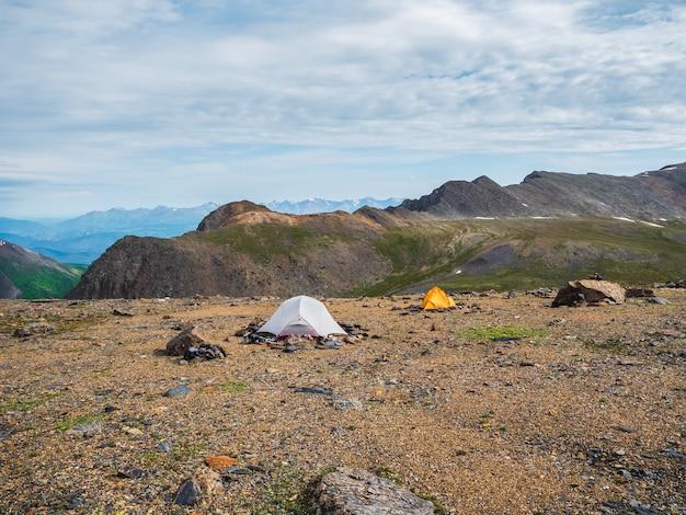 바위가 많은 고지대에서 캠핑. 높은 산의 배경에 두 개의 텐트입니다.