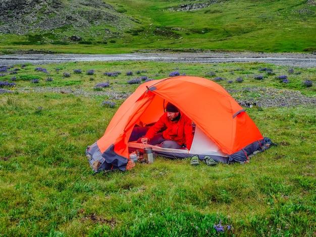 夏の緑の高地高原でのキャンプ。オレンジ色のテントの男が食事を準備しています。自然の中での平和とリラクゼーション。ソロハイキングのコンセプト。