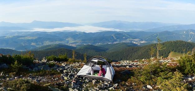 明るい夏の朝に山の頂上でキャンプ