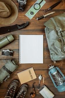 キャンプやハイキングコピースペースを持つ素朴な木製の背景にブーツやバックパックを含む流行に敏感なギア