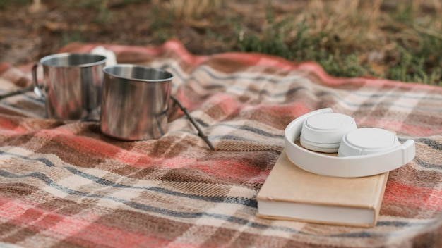 Camping outdoors with book and mugs for hot drinks