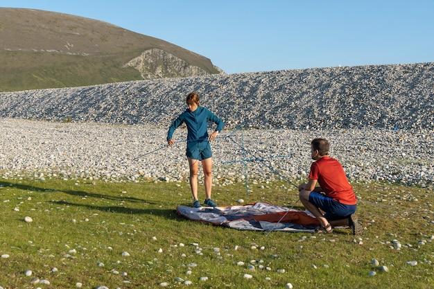 自然の岩のビーチにテントを張るキャンプの人々のアウトドアライフスタイルのカップル