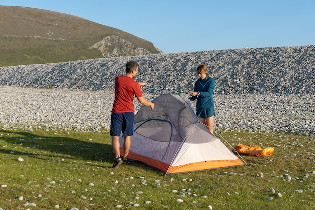 Кемпинг люди на открытом воздухе образ жизни пара, ставя палатку на скалистом пляже природы.