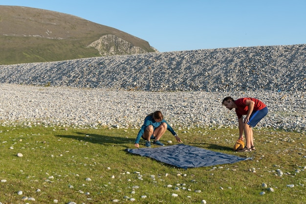 Camping people outdoor lifestyle couple putting up a tent in nature rocky beach.