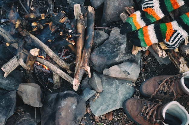 Camping rest concept knitted socks hiking boots are drying near a campfire in the forest