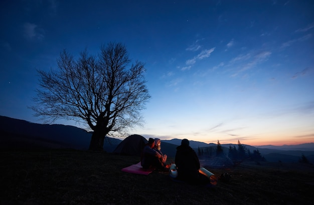 Camping site in mountains at dawn. group of three young tourists sitting in front of tent and meeting early morning watching sky red from rising on horizon sun. tourism and traveling concept.