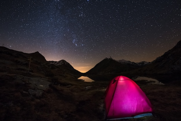 Camping under starry sky and milky way arc at high altitude on the italian french alps