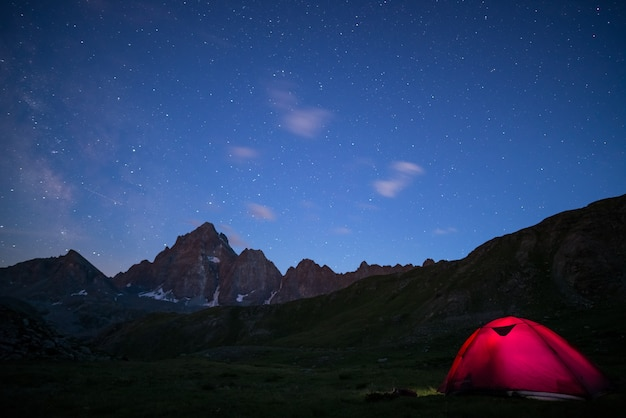 Camping under starry sky and milky way at high altitude on the alps.
