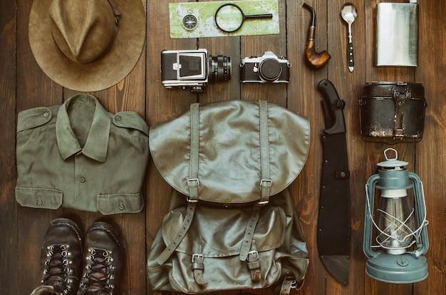 木製の背景に配置されたキャンプ用品。マチェーテ、シャツ、ブーツ、ランタン、禁煙パイプ、帽子、地図、コンパス。ハイキングコンセプトの準備。トレッキングはがき、ポスター、バナー。