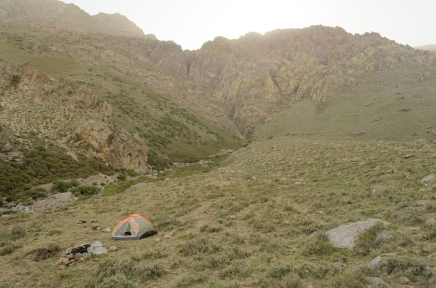 Camping tent among the mesmerizing mountains under a cloudy sky