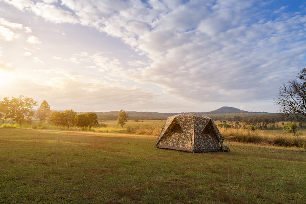 Camping tent on green field near forest during dramatic sunrise at summer misty morning, concept of outdoor camping adventure