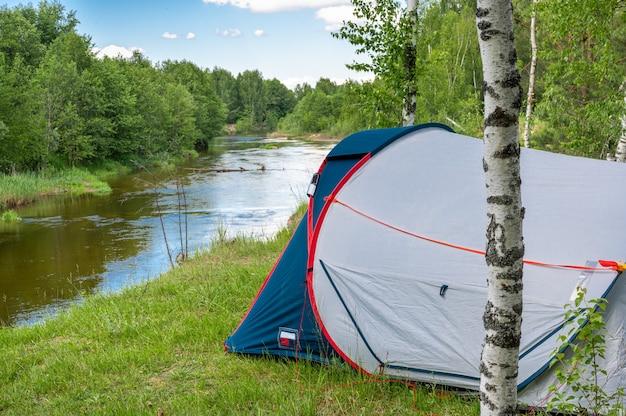 강 옆 숲에서 캠핑 텐트. 숲에서 관광 텐트입니다. 관광 배경입니다. 자연 관광, 라이프 스타일 및 캠핑 휴가 개념