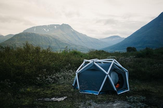 キャンプテント、インフレータブル構造が山の側面に立っており、アウトドアの雰囲気を生きるライフスタイルのための美しく刺激的なキャンプの場所