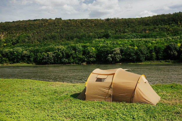 Camping tent near mountain river in the summer sunny day. beige camping tent on river beach.