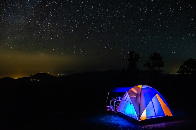 The camping tent in the night mountain under a starry sky