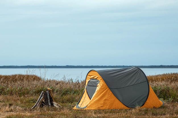 Camping tent in orange  nature and the lake.  travel, tourism, camping.