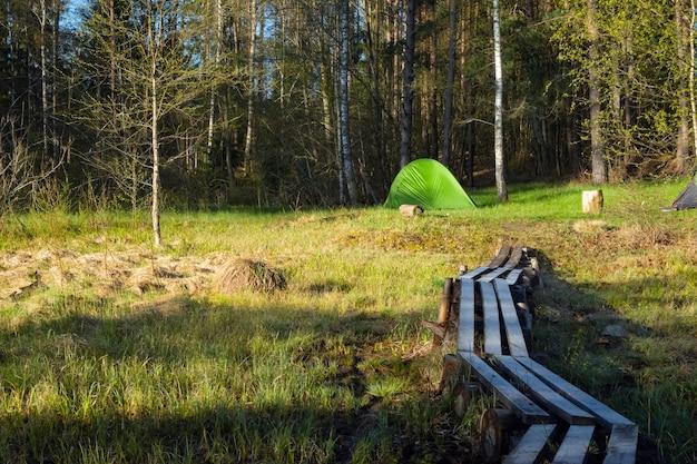 Кемпинговая палатка разбита у озера в лесу. отдых на турбазе на природе.