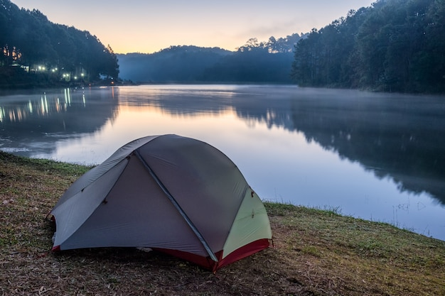 Camping tent tranquil on reservoir at dawn