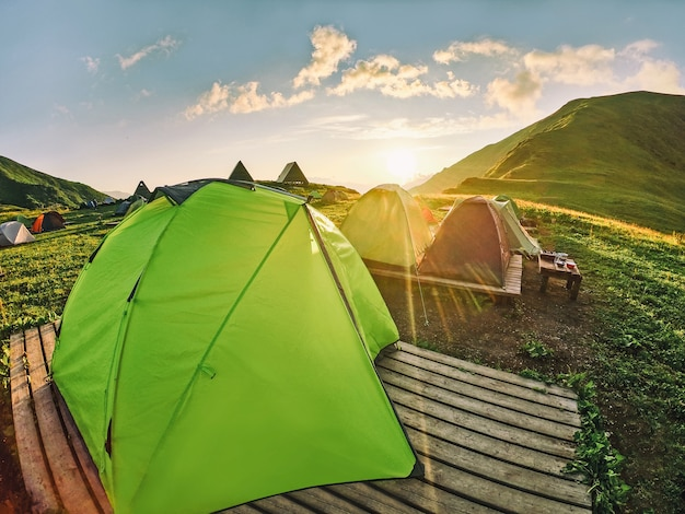 Camping tents on wooden platforms in campsite at sunlight background