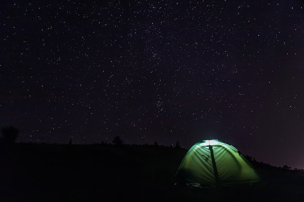 Camping tourist tent with light inside under the starry sky