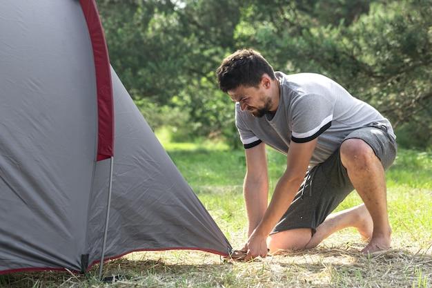 캠핑, 여행, 관광, 하이킹 개념 - 젊은 남자가 숲에 텐트를 치고 있습니다.