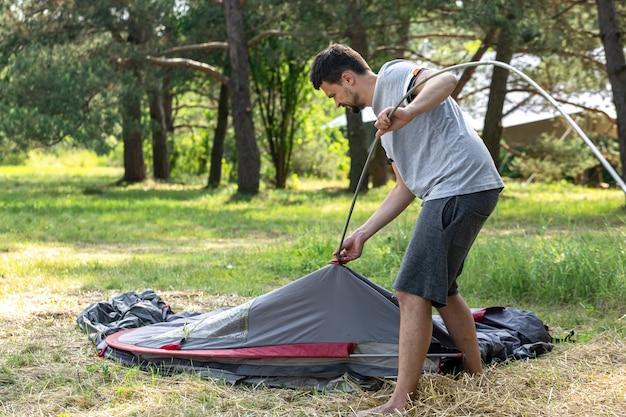 キャンプ、旅行、観光、ハイキングのコンセプト-若い男が屋外でテントを張る。