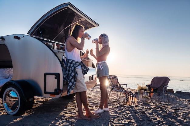 キャンプ旅行。朝の朝食を食べてお茶を飲むキャンプ旅行でリラックスしたカップル
