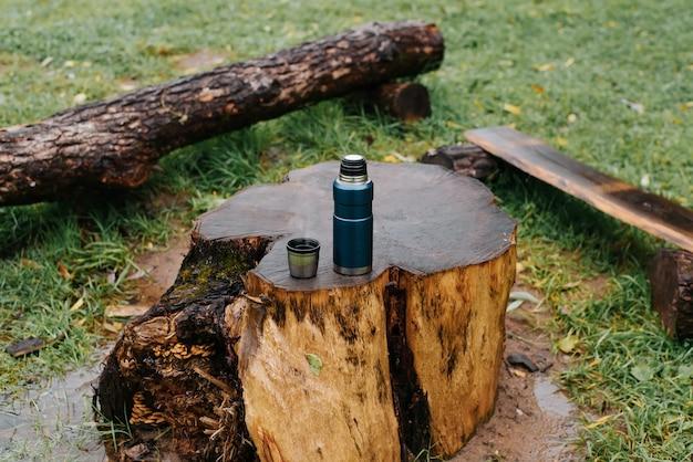 Кемпинг вакуумный термос и кружка горячего напитка, стоящая на пне в кемпинге в дождливую осеннюю погоду. походы, кемпинг, согревающий напиток в концепции холодного сезона.