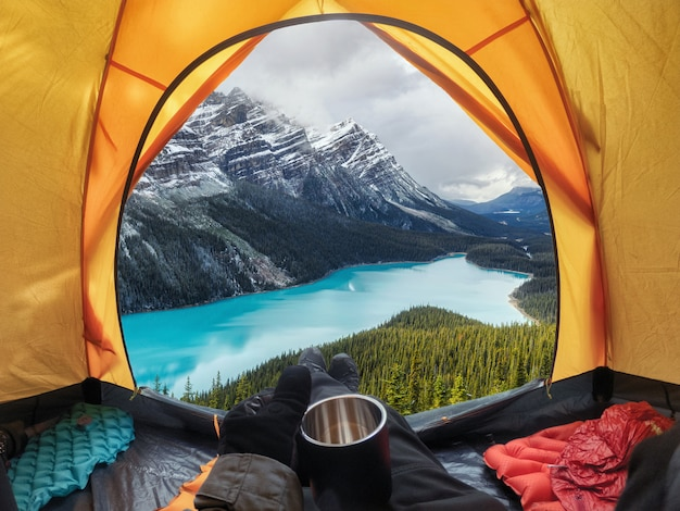 Camping with holding cup in yellow tent open with peyto lake in icefields parkway