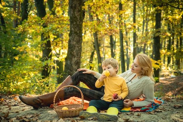 秋が好きな秋の公園で屋外で過ごす幸せな母と息子の子供たちとのキャンプ...