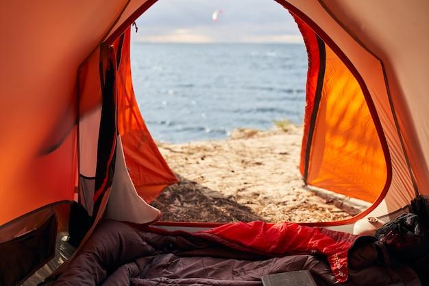 침낭 캠핑은 해변에서 나오는 문과 자연의 파도가있는 위치에 있습니다.