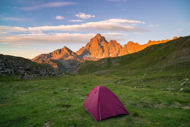 Camping with tent on the alps. scenic sky at sunset. adventure conquering adversity.
