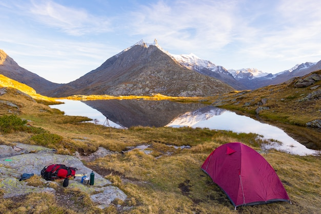 Camping with tent near high altitude lake on the alps
