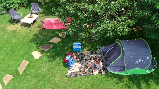 Campsite aerial view from above, mother and daughter having fun, tent and camping equipment under tree, family vacation in camp outdoors concept