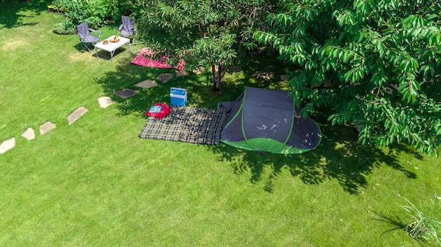 Campsite aerial view from above tent and camping equipment under tree family vacation in camp outdoors concept