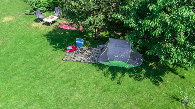 Campsite aerial view from above, tent and camping equipment under tree