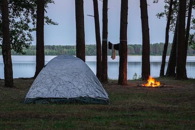 Кемпинг у озера в сумерках, палатка и место для костра у воды в окружении деревьев в лесу.