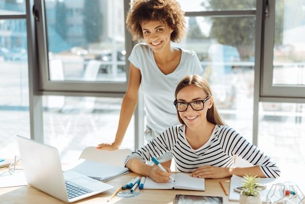 캠퍼스 일. 쾌활한 아름다운 젊은 여자가 테이블에 앉아 그녀의 국제 친구와 함께 공부하는 동안 기쁨을 표현