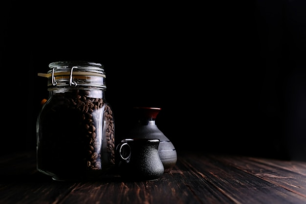 A can of coffee, a cup and a turk on a wooden table, on a black background.