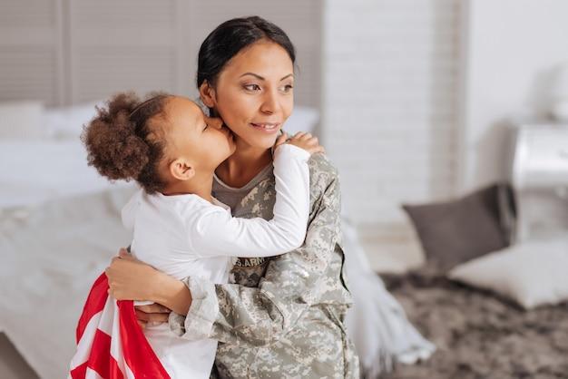 Можно наконец расслабиться. изящная уверенная в себе молодая мать обнимает своего маленького ребенка после работы вдали от дома, в то время как ее дочь целует ее в щеку