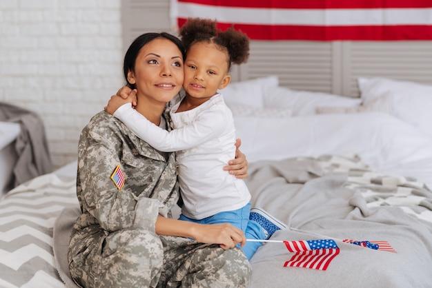 Могу наконец отдохнуть. замечательно привязанная молодая мать и ее ребенок, представляющие, что проведут следующие несколько недель вместе, сидя на кровати и обнимая друг друга