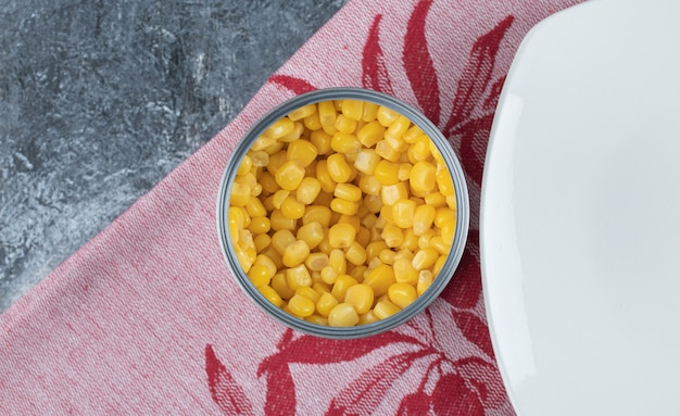 A can full of popcorn seeds with empty plate on tablecloth .
