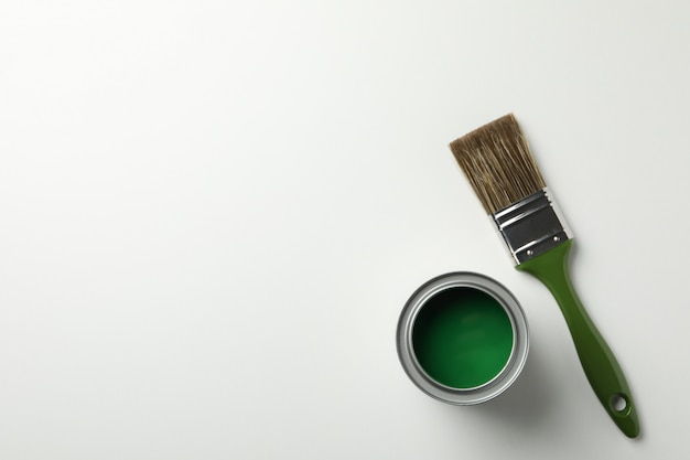 Can of green paint and brush on white surface