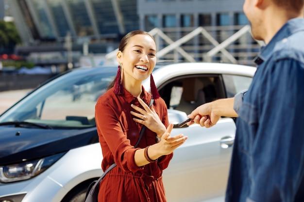 運転できますか。車から鍵を取りながら彼氏を見ているポジティブな若い女性
