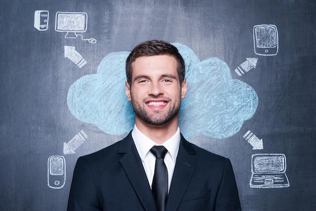 ガジェットのない生活は想像できません。黒板に描くチョークに立ち向かいながら笑顔でカメラを見ているハンサムな若い男