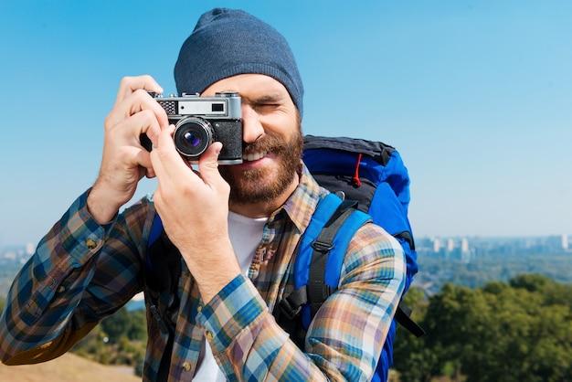 そんな美しい景色は見逃せません。バックパックを背負って景色の写真を撮るハンサムな若い男